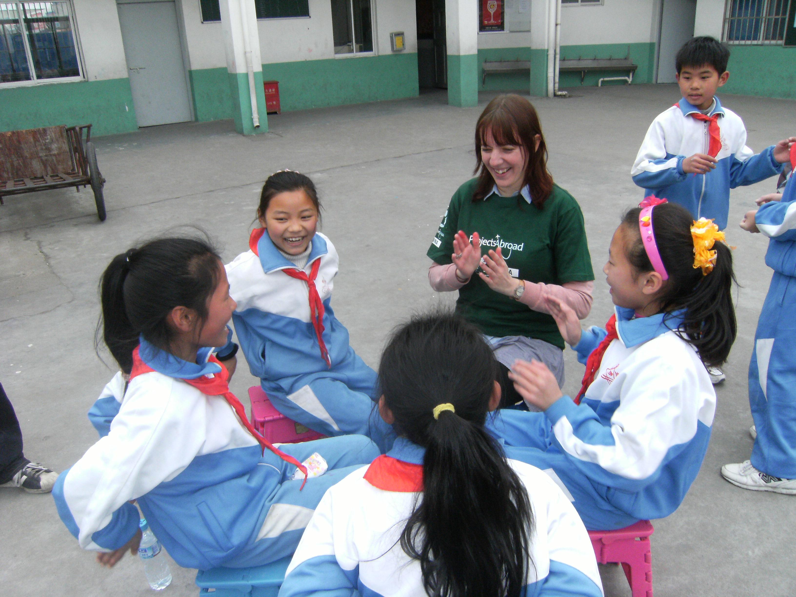 Projects Abroad volunteer with children in China claps with children outside her kindergarten placement.